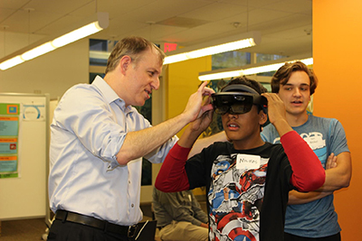 Brian Moynihan helping a student use the Microsoft HoloLens